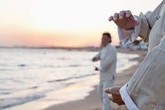 实践在海滩的两位老人太极拳在日落,关闭在手上 免版税库存照片