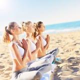 实践在海滩的小组妇女瑜伽 免版税图库摄影