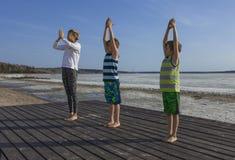 实践在海滩的少妇和两个孩子瑜伽 免版税图库摄影