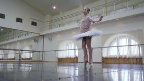 实践在舞蹈演播室或健身房的白色芭蕾芭蕾舞短裙礼服的芭蕾舞女演员 跳舞在类的妇女古典舞步 单独 股票录像