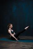 实践在蓝色席子的瑜伽妇女户内 免版税库存图片
