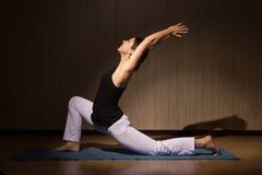 实践她的力量和平衡的瑜伽妇女 免版税库存照片