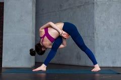 实践常设侧角转弯位置的运动的白种人妇女在瑜伽类期间 库存照片