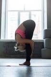 实践常设向前弯瑜伽姿势的妇女 库存图片