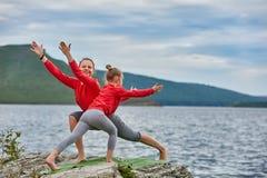 年轻实践母亲和小的女儿平衡在岩石的瑜伽姿势在河附近 免版税库存图片