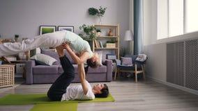 实践瑜伽位置的逗人喜爱的夫妇学生在家一起行使 股票录像