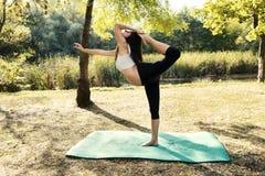 实践瑜伽形状孕妇 免版税图库摄影
