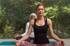 实践瑜伽的两名妇女 免版税库存图片