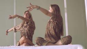 实践瑜伽的两名年轻瑜伽妇女画象在明亮的演播室摆在 股票视频