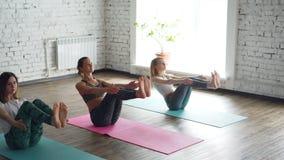 实践瑜伽的小姐平底锅射击做平衡的小船姿势在轻的宽敞的房间 少妇被注重  影视素材