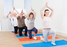 实践瑜伽的教练员和顾客在健身房 免版税库存图片