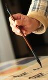 实践画笔callingraphy人老的笔使用 免版税库存照片