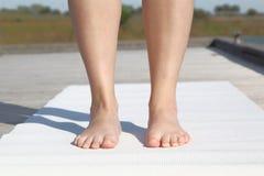 实践的瑜伽 在席子的妇女常设外部 免版税库存照片