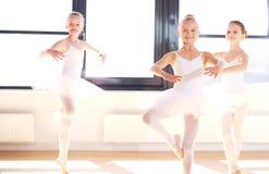 实践竖趾旋转的小组年轻芭蕾舞女演员 库存图片