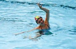 实践花样游泳的水池的女孩 免版税图库摄影