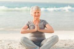 实践高级女子瑜伽的海滩 免版税库存照片