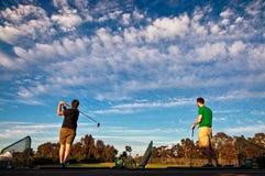 实践他们的高尔夫球的两个人摇摆在开车范围 免版税库存照片