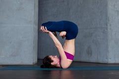 实践Hatha瑜伽的先进的年轻yogini站立在被倒置的莲花姿势, padmasana,在席子 免版税库存图片