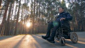 实际上挑战人移动沿路的一个供给动力的轮椅 股票录像