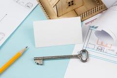 实际概念的庄园 与房子形象和空白的名片的银色钥匙在蓝色背景 顶视图 免版税图库摄影