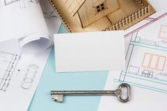 实际概念的庄园 与房子形象和空白的名片的银色钥匙在蓝色背景 顶视图 免版税库存图片