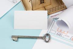 实际概念的庄园 与房子形象和空白的名片的银色钥匙在蓝色背景 顶视图 免版税库存照片