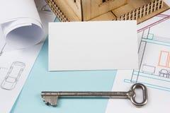 实际概念的庄园 与房子形象和空白的名片的银色钥匙在蓝色背景 顶视图 图库摄影