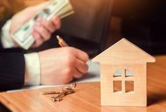 实际概念的庄园 住房销售或租务,公寓租务 地产商 签公寓合同 100个票据概念美元房子做抵押 库存图片