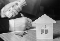 实际概念的庄园 住房销售或租务,公寓租务 地产商 签公寓合同 100个票据概念美元房子做抵押 星期一 库存照片