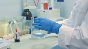 实验员在明亮的实验室混合在烧瓶的试剂 股票录像