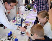 实验室化学家达每在教关于化学作为英国词根一部分,科学,技术,引擎的孩子的实验室外面的天 免版税库存照片