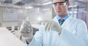 实验室外套有玻璃设备的和白色图表的人与反对模糊的实验室的火光 免版税库存照片