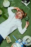 实验室外套的女孩有说谎在黑板的放大镜的 图库摄影