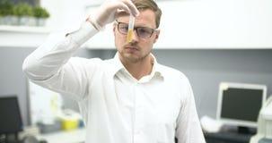 实验室审查的液体的科学家在玻璃烧杯 股票视频