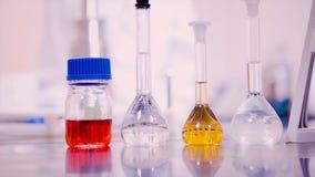 实验室烧瓶和烧杯有不同的颜色液体的在实验室桌上 免版税图库摄影