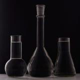 实验室设备,在黑背景的三块玻璃烧瓶 库存照片