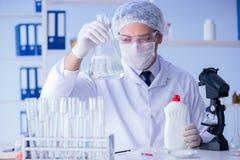 实验室试验新的清洁解答洗涤剂的人 免版税图库摄影