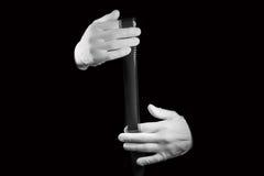 实验室,在白色手套的手拿着一部黑白影片 免版税图库摄影