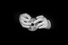 实验室,在白色手套的手拿着黑色和影片,暗房, developmen 免版税图库摄影