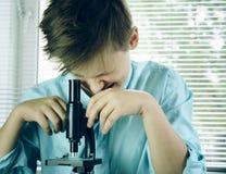 实验室 专心地看通过显微镜的滑稽的男孩 特写镜头 免版税库存照片