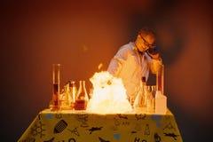 实验教授在实验室里,与爆炸的举办的化工 免版税库存照片