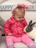 宠爱一只活兔子的兔宝宝耳朵的女婴 免版税库存照片