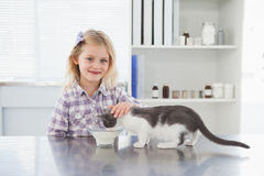 宠爱她的猫饮用奶的愉快的所有者 免版税库存照片