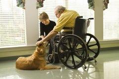 宠爱妇女的狗年长人 免版税库存图片