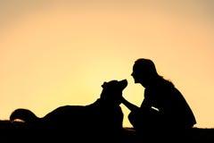 宠爱德国牧羊犬狗剪影的愉快的妇女 免版税库存图片