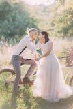 宠爱的新婚佳偶夫妇的可爱的画象面孔 新郎坐在晴朗的自行车 库存照片