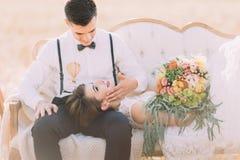 宠爱说谎的面孔新郎的特写镜头画象在他的晴朗的领域的膝部新娘 免版税库存照片