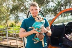 宠物、家畜、季节和人概念-愉快的人画象有走他的奇瓦瓦狗的狗的户外 库存图片