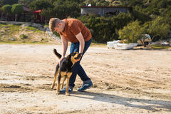 宠物、家畜、季节和人概念-有走他的狗的愉快的人户外 免版税库存照片