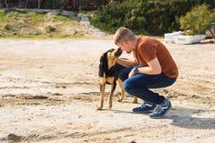 宠物、家畜、季节和人概念-有走他的狗的愉快的人户外 免版税图库摄影
